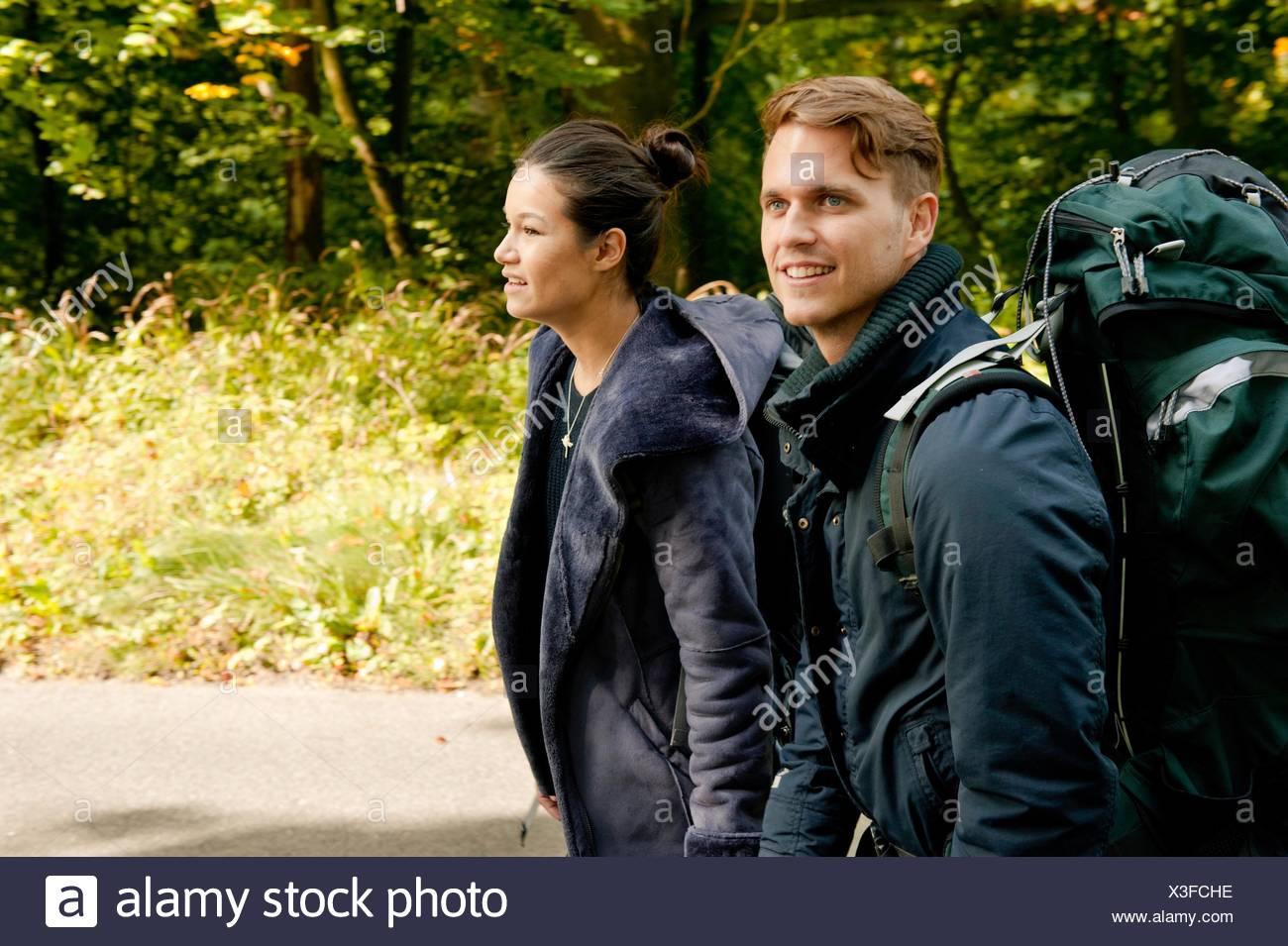 Coppia giovane escursionismo su strada rurale Immagini Stock