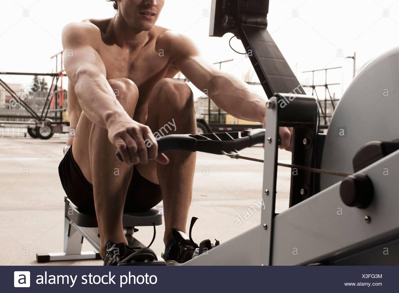 Uomo che utilizza attrezzature per esercizi in palestra Immagini Stock