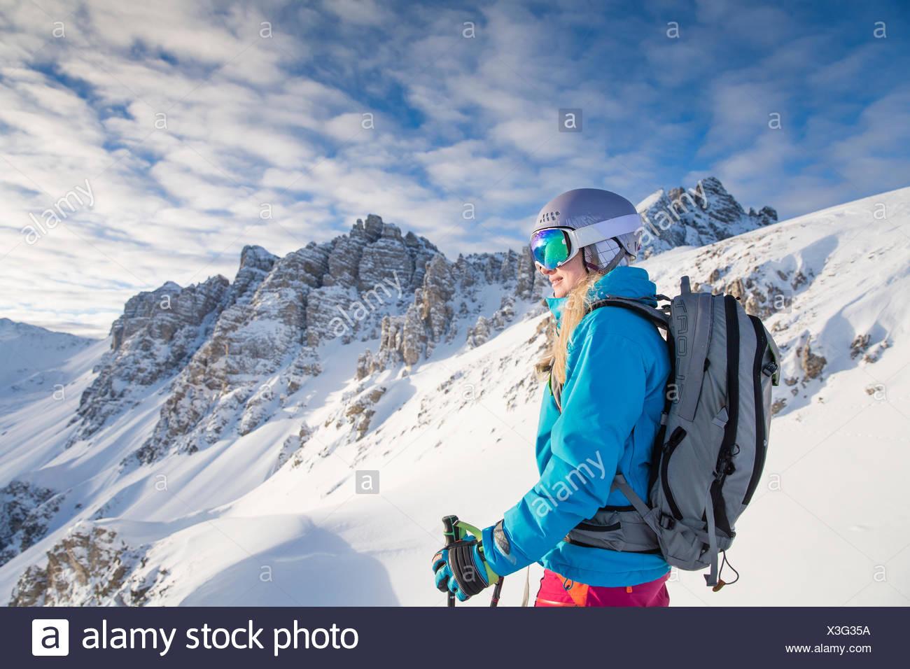 Lo sciatore, con rifiniture con maschere da sci e casco guardando in lontananza, Kalkkögel dietro, Axamer Lizum, Tirolo, Austria Immagini Stock