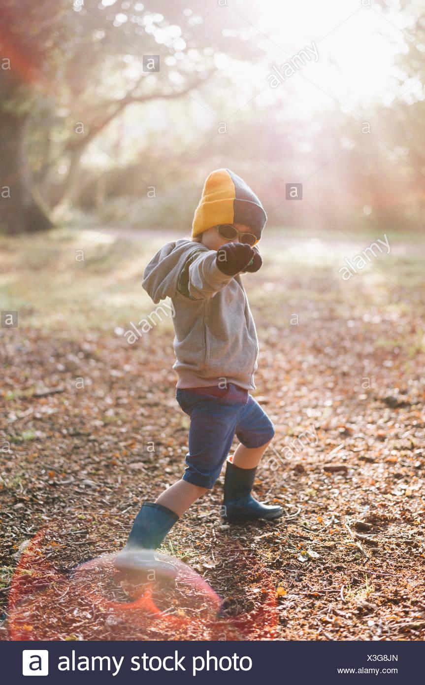 Un ragazzo all'aperto in un cappellino di indossare pantaloncini corti e gli stivali da pioggia, colpendo una posa con un braccio teso. Immagini Stock