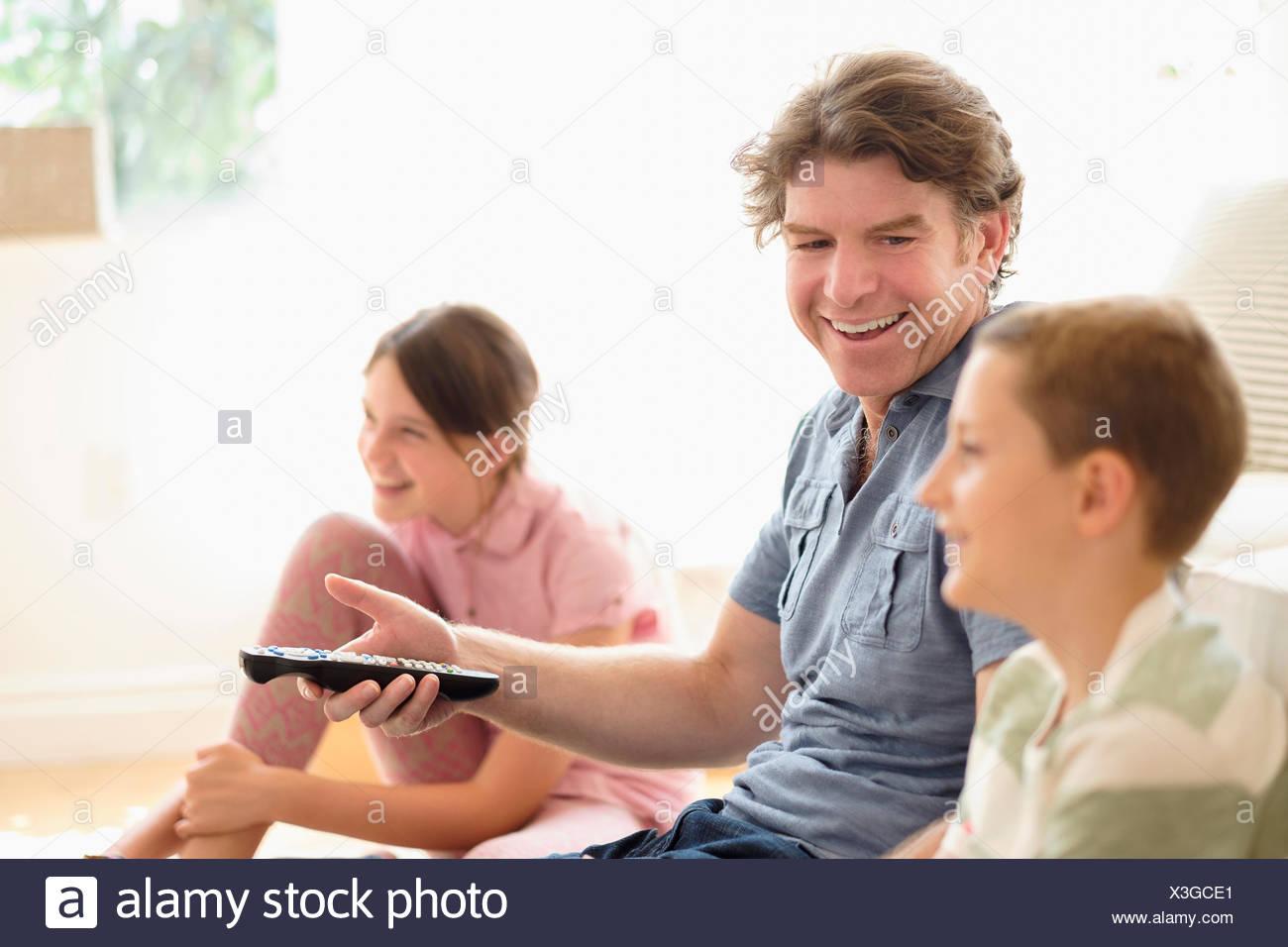 Bambini (8-9, 10-11) guardando la TV con il loro padre Foto Stock