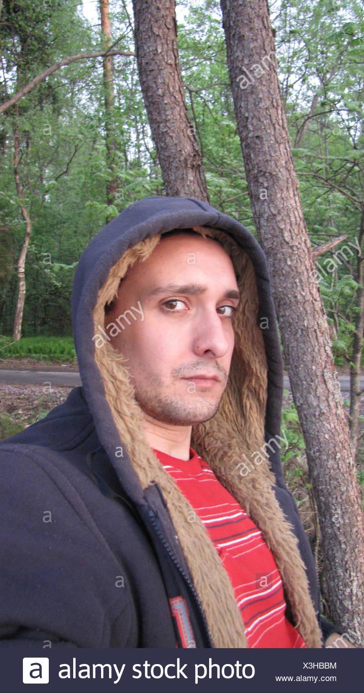 Giovane uomo che indossa Felpa con cappuccio Relax nel parco Immagini Stock