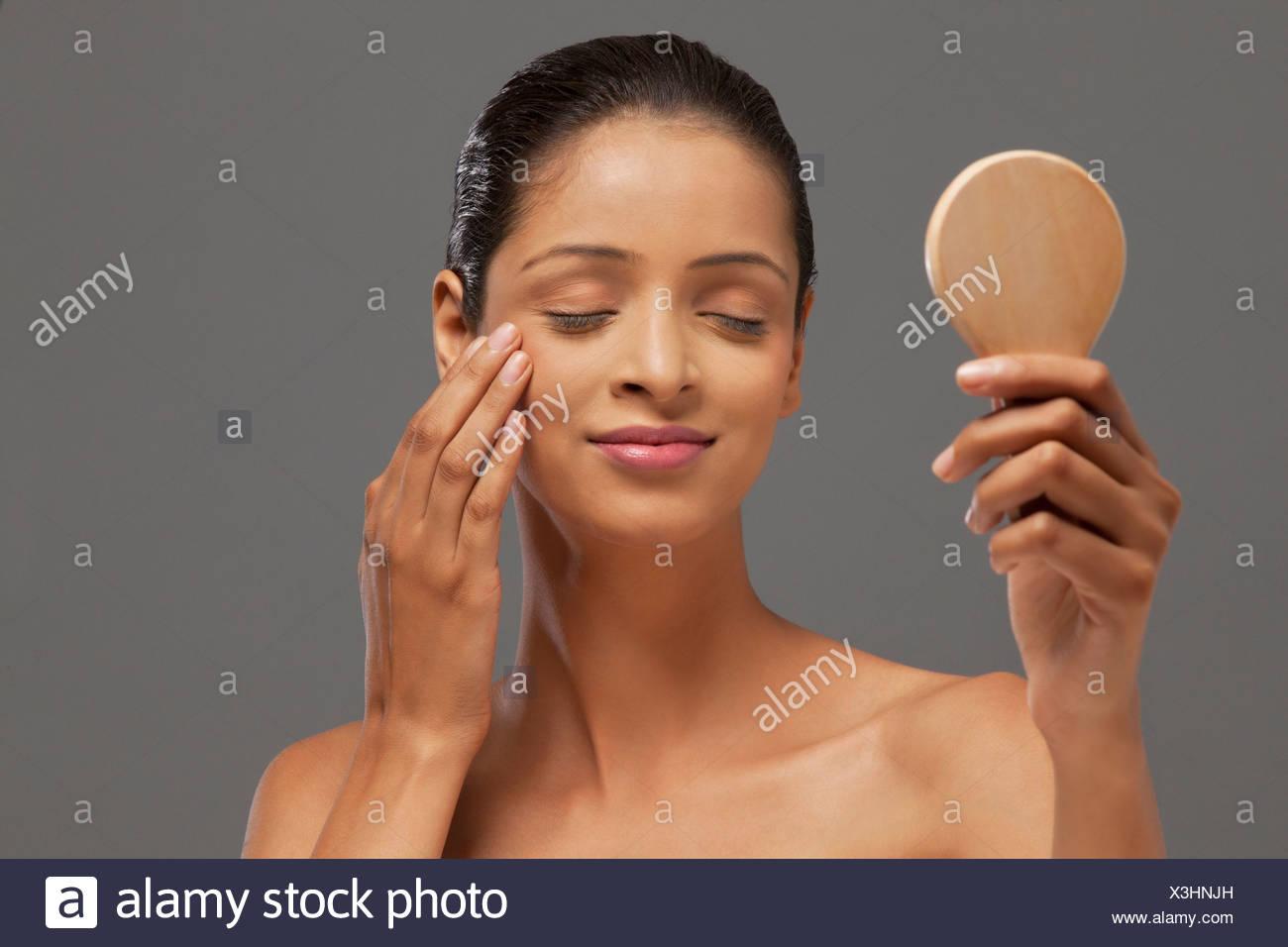 Giovane donna con gli occhi chiusi tenendo lo specchio a mano Immagini Stock