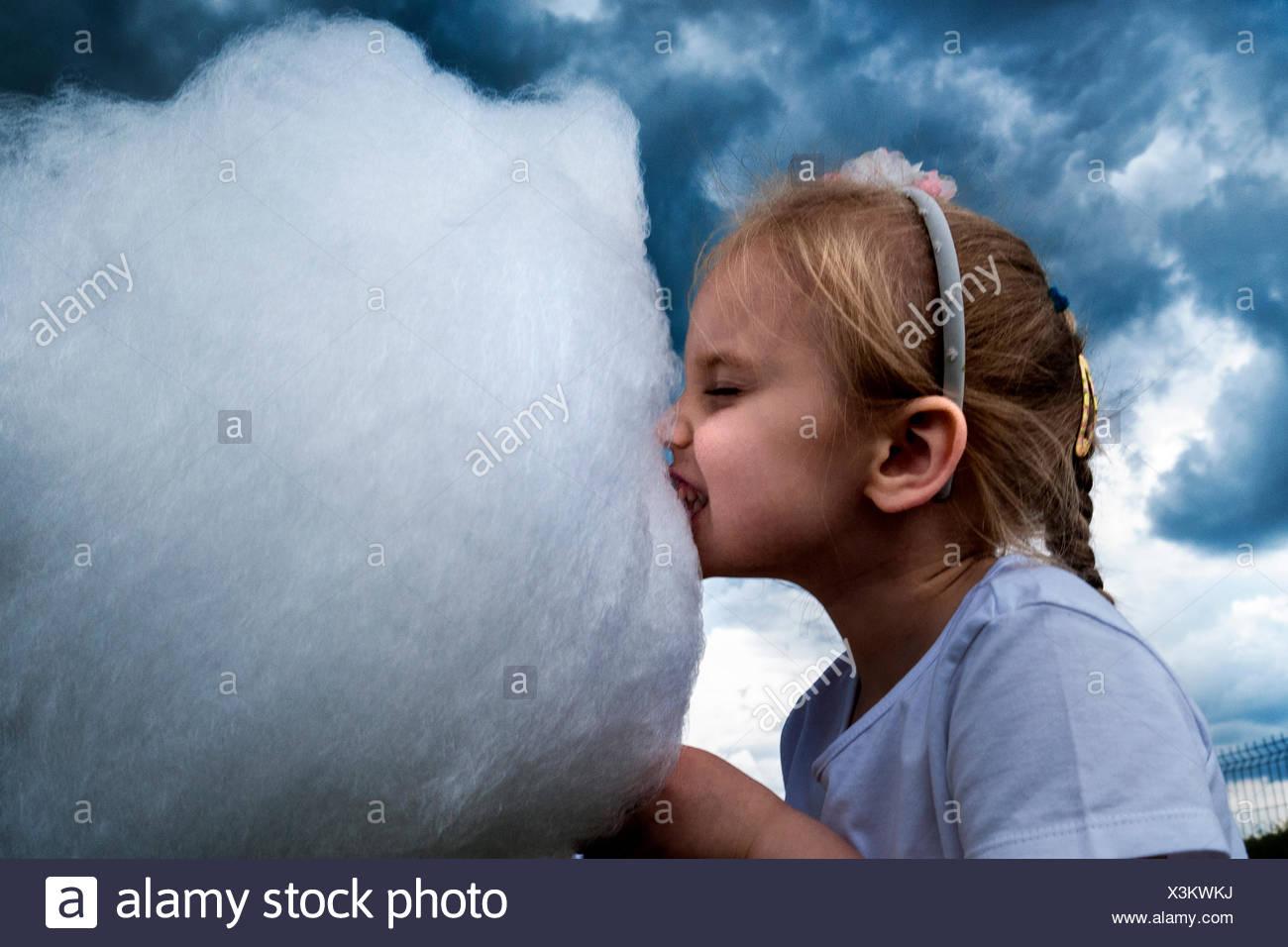Bambina mangiando caramelle di cotone con drammatica sky dietro di lei Immagini Stock