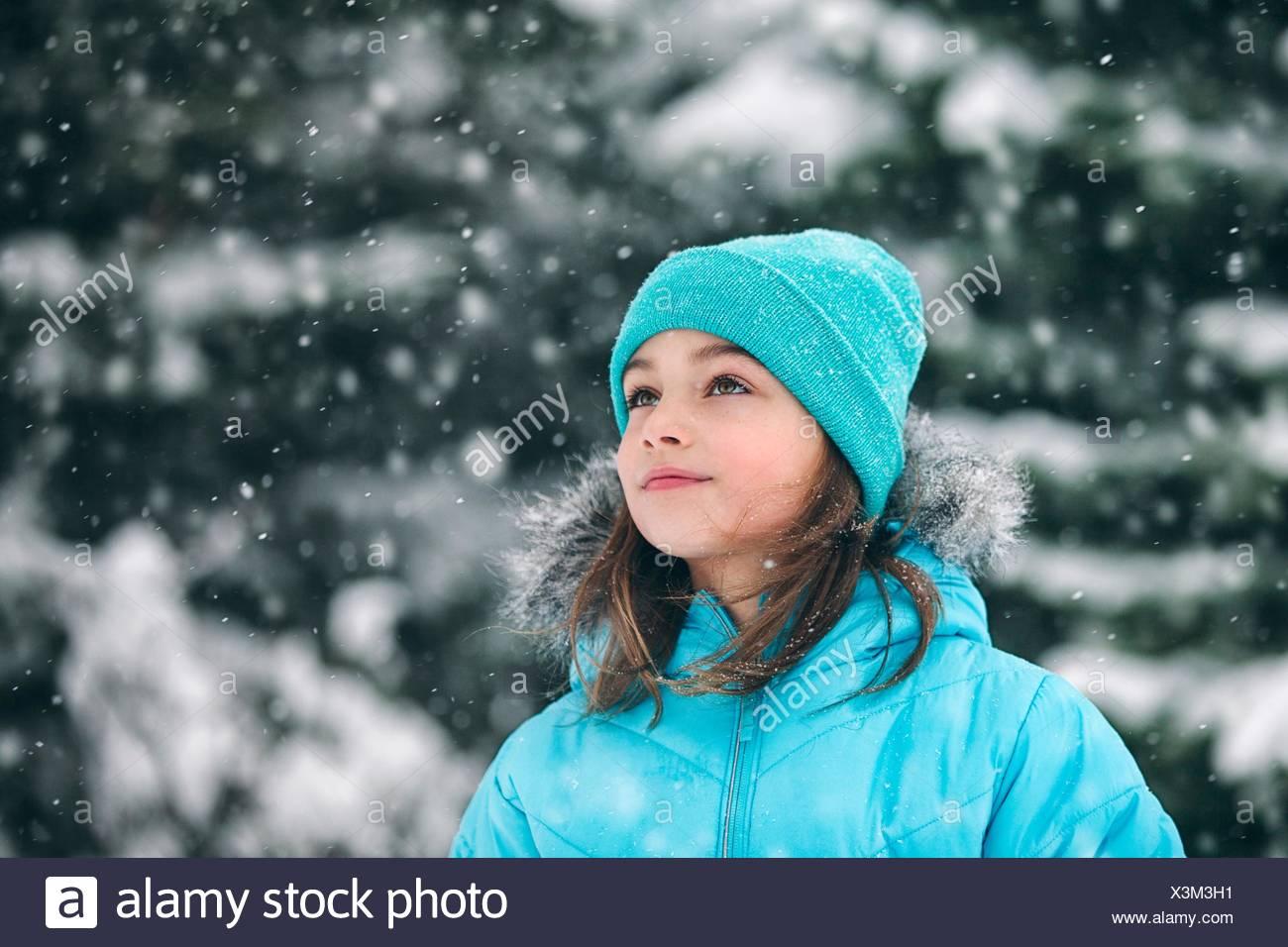 Ragazza indossando knit hat guardando lontano, nevicava Immagini Stock
