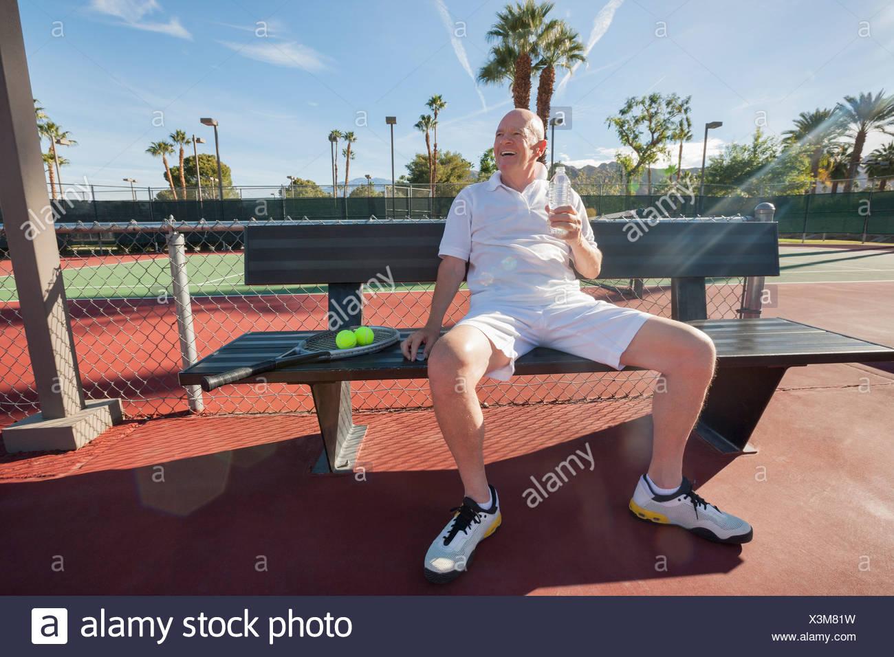Felice senior tennista con acqua in bottiglia seduta sul banco a corte Immagini Stock