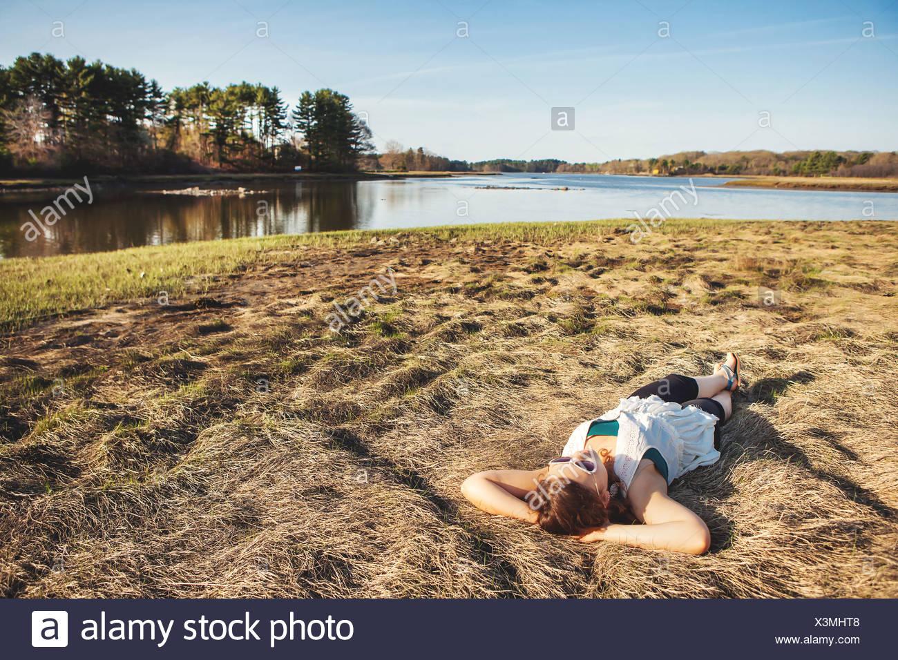 Giovane donna a prendere il sole sul prato in Kittery, Maine, Stati Uniti d'America Immagini Stock
