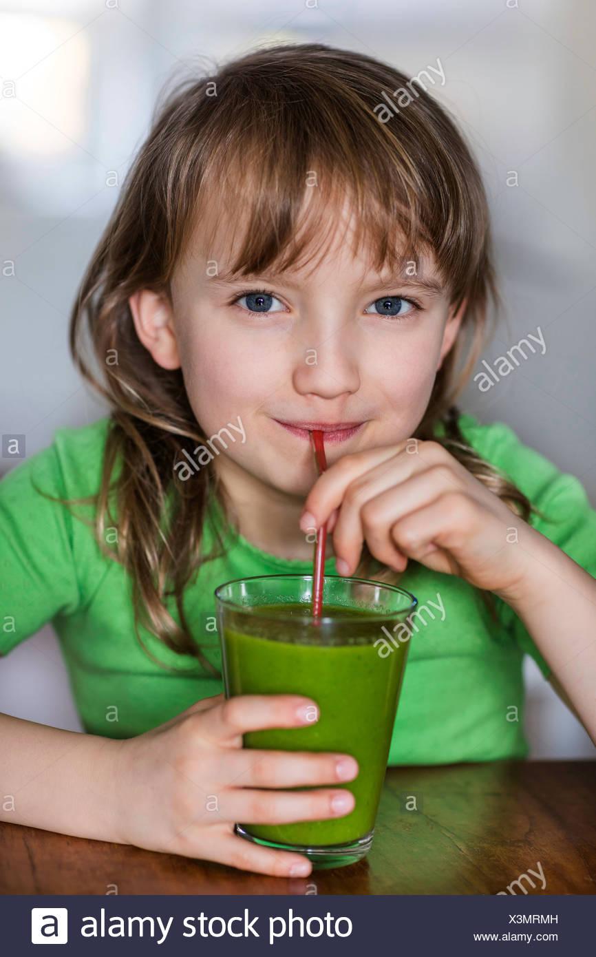 Ritratto di ragazza di bere un bicchiere di succo di verdura Foto Stock