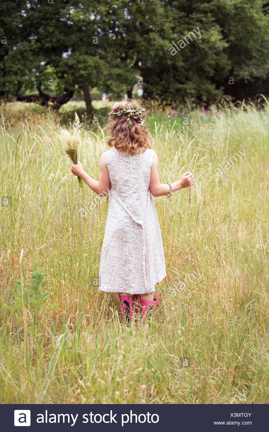 Ragazza giovane con fiori nei capelli picking fiori selvatici in un prato. Immagini Stock