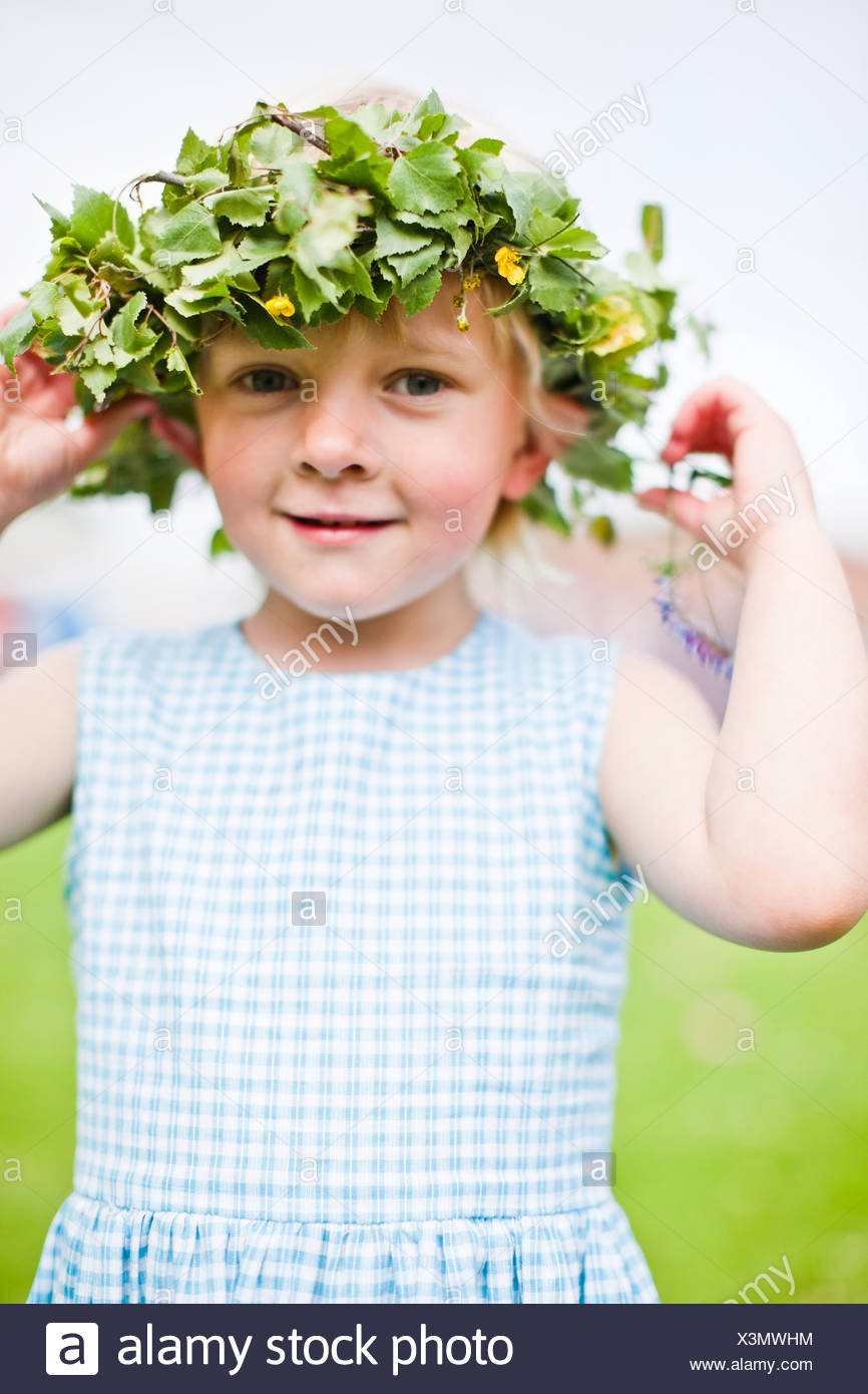 Ragazza sorridente indossando ghirlanda di fiori Immagini Stock