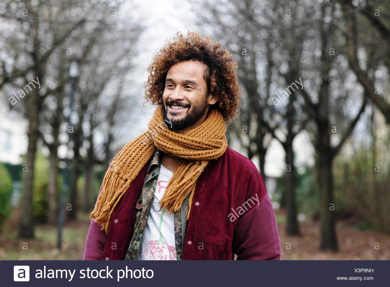 Ritratto di uomo sorridente con anellini colorati in natura Immagini Stock