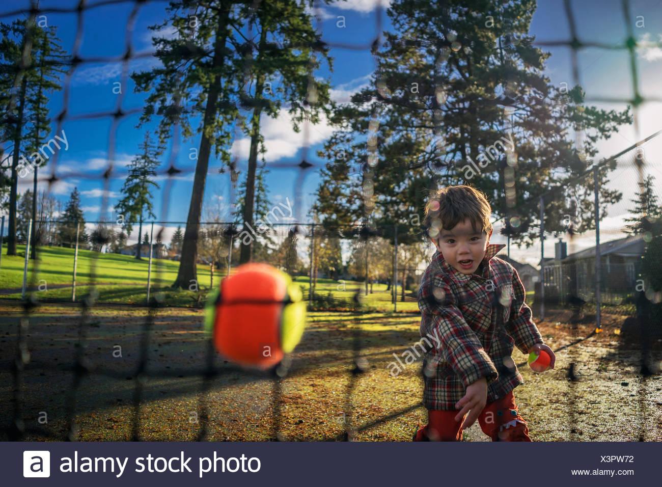 Ragazzo giovane gettando palla da tennis al netto Immagini Stock