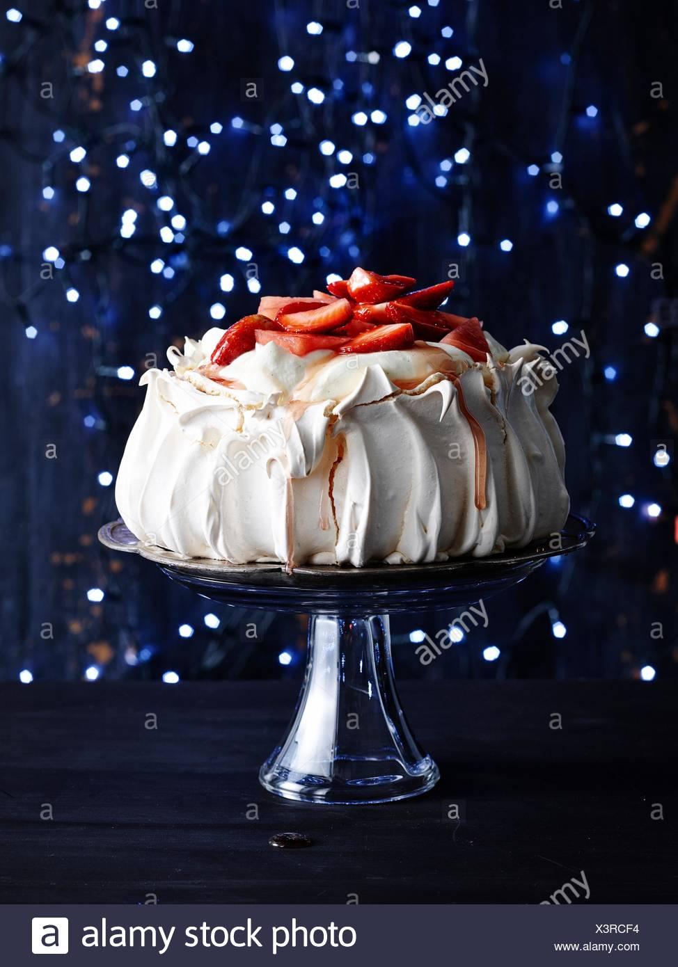 Fragole coperte pavlova sulla torta di vetro sostare di fronte vivace sfondo blu scuro Immagini Stock