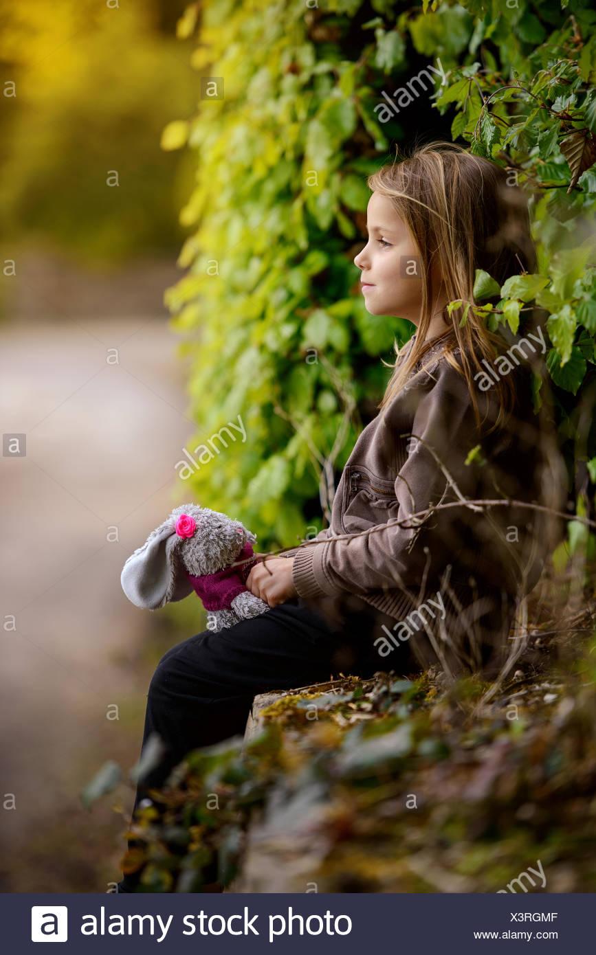 Vista laterale di una ragazza con un coniglietto ripiene toy Immagini Stock