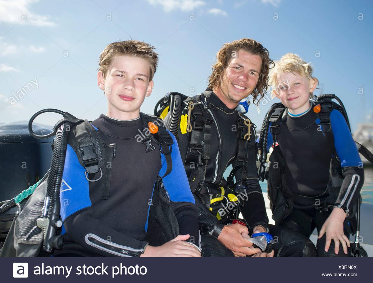 Ritratto di due ragazzi con metà maschio adulto scuba diving insegnante Immagini Stock