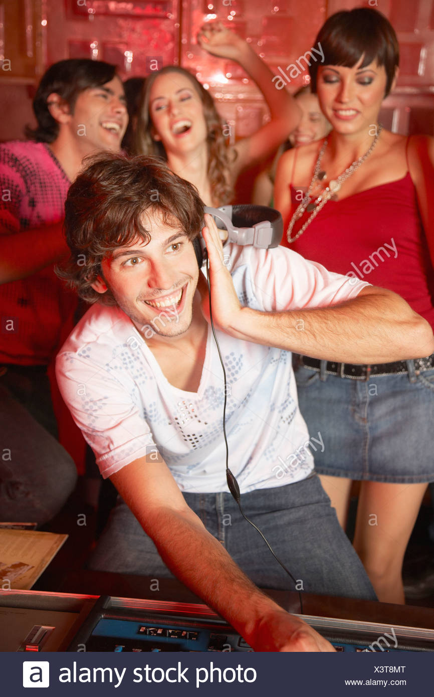 Disc jockey in discoteca con persone che ballano intorno a lui sorridente Immagini Stock