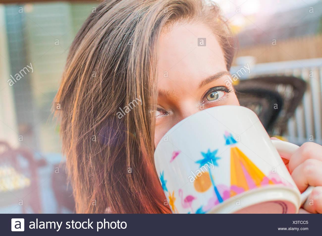 Close up della giovane donna di bere il caffè dalla tazza Immagini Stock