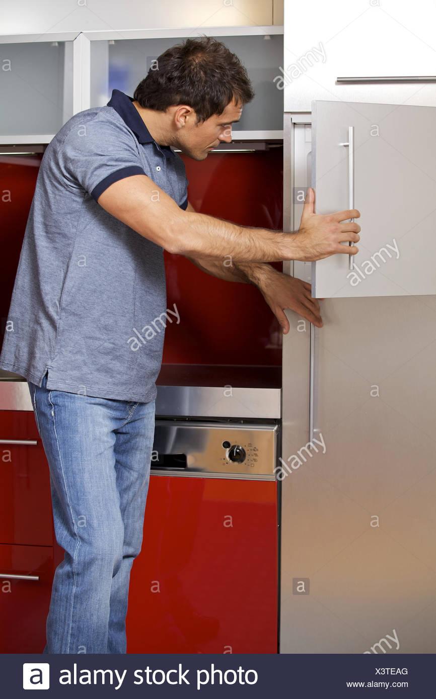 Oung uomo cercando in frigorifero Immagini Stock