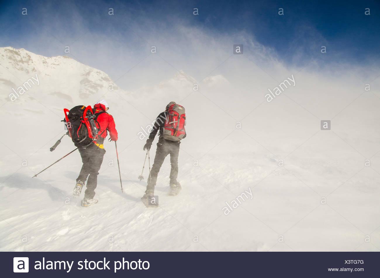 Gli alpinisti in anticipo il vento freddo (Valle Soana, il Parco Nazionale del Gran Paradiso, PIEMONTE) Immagini Stock