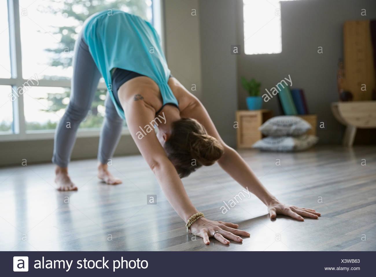 La donna a praticare yoga nella posizione del Cane con la testa in giù pongono Immagini Stock