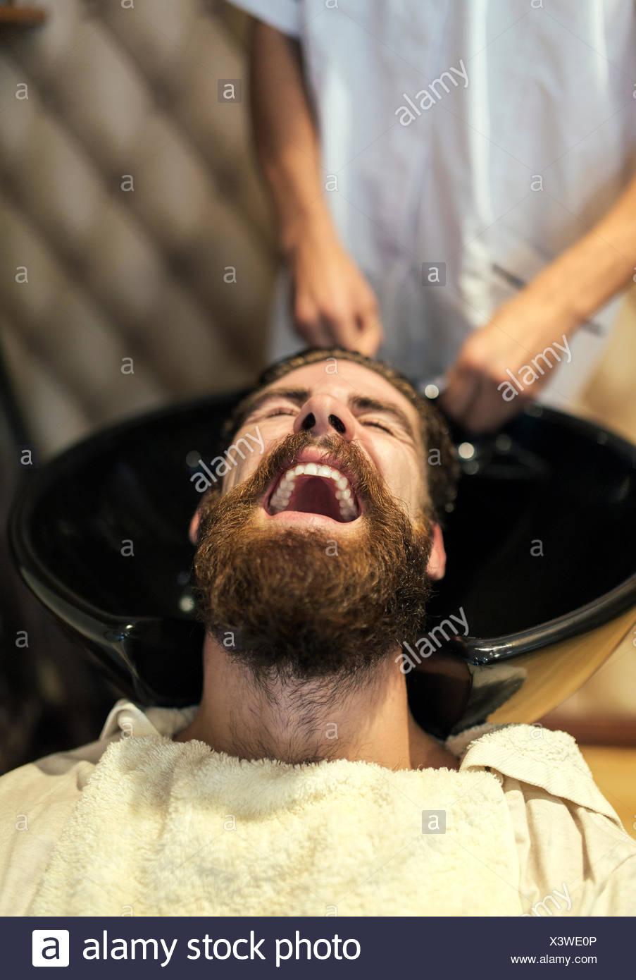 Barbiere di lavaggio dei capelli di un cliente con la bocca aperta Immagini Stock