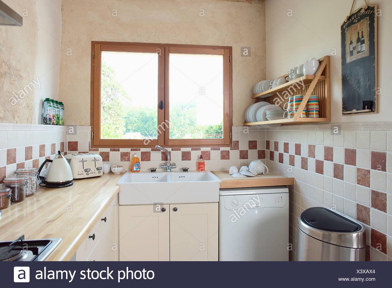 Finestra sopra lavello e lavastoviglie in economia piccola cucina