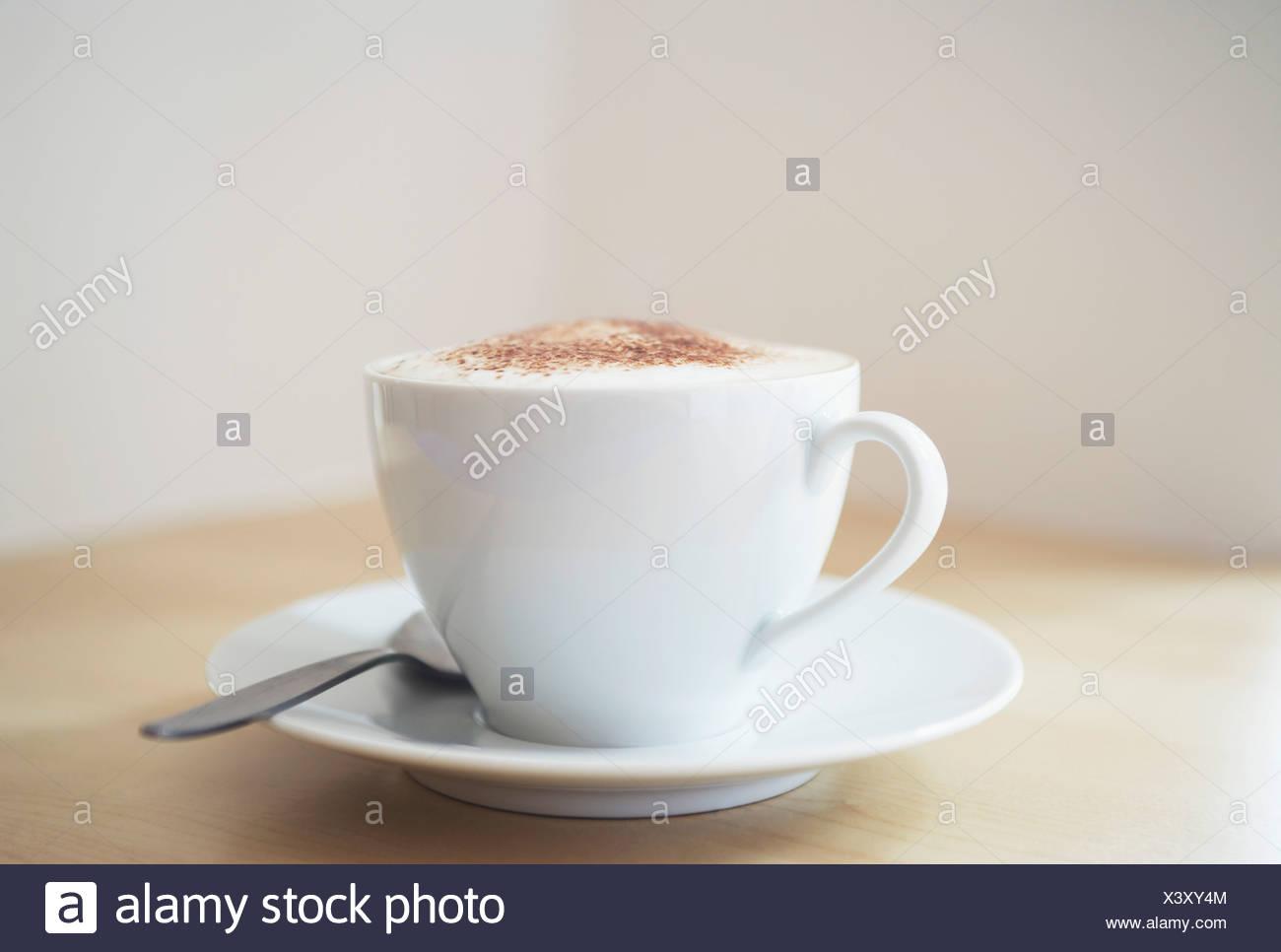 White tazza di cappuccino sul tavolo di legno, close-up Immagini Stock
