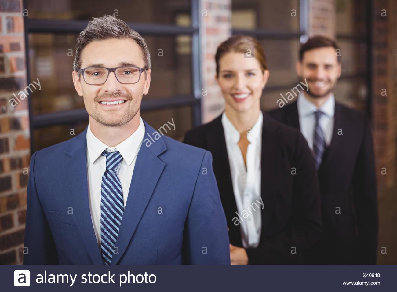 Felice la gente di affari in piedi in fila Immagini Stock
