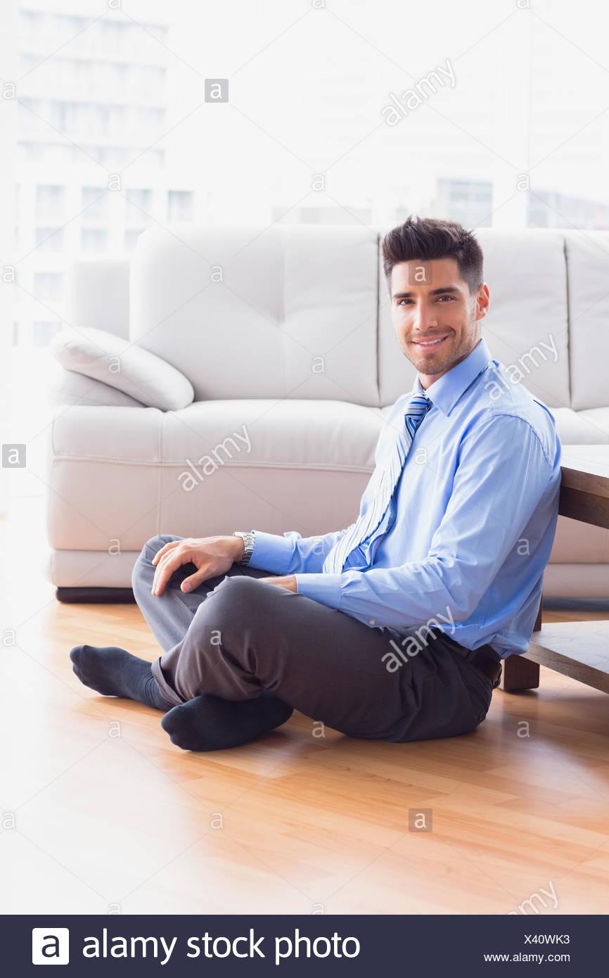 Imprenditore bello seduto sul pavimento Immagini Stock