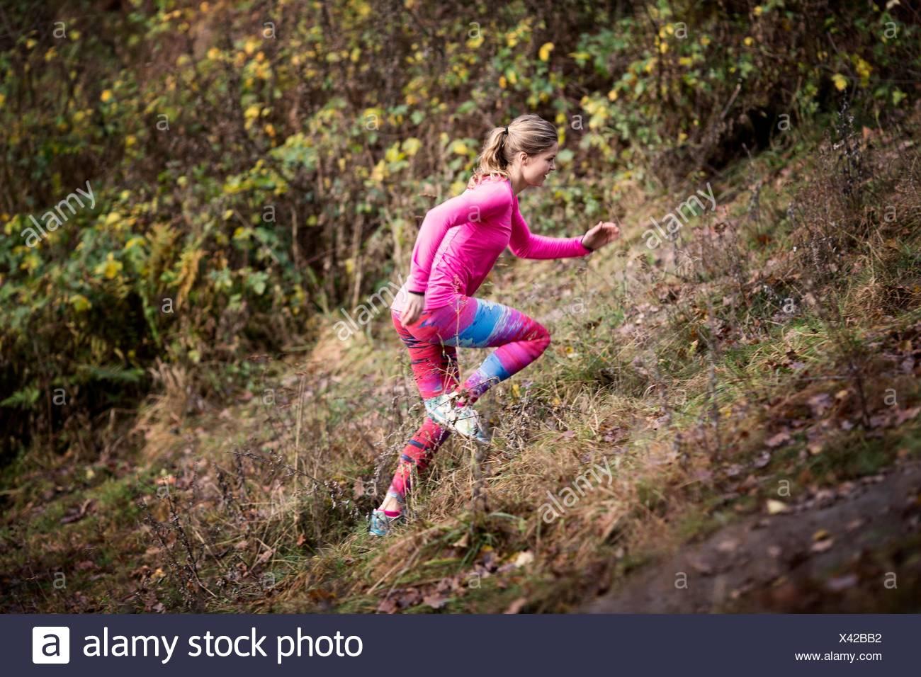 Vista laterale della giovane donna che indossa lo sport wear in esecuzione su per la collina Immagini Stock