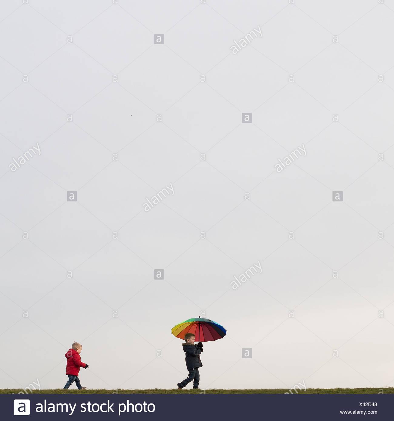 Ragazzi a piedi, con ombrello Immagini Stock