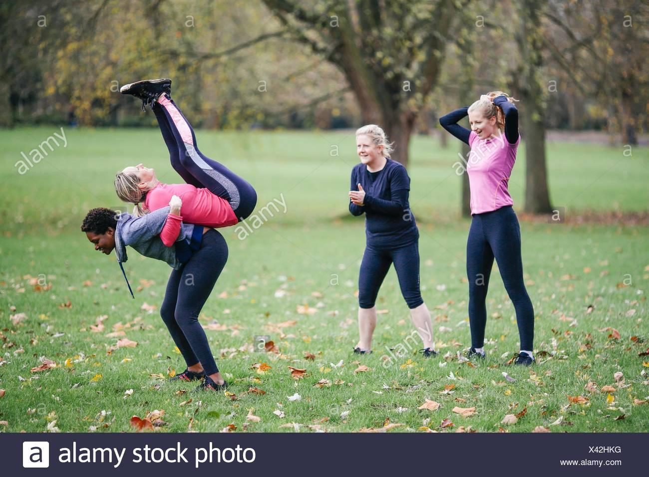 Le donne e i giovani facendo warm up esercizi in posizione di parcheggio Immagini Stock
