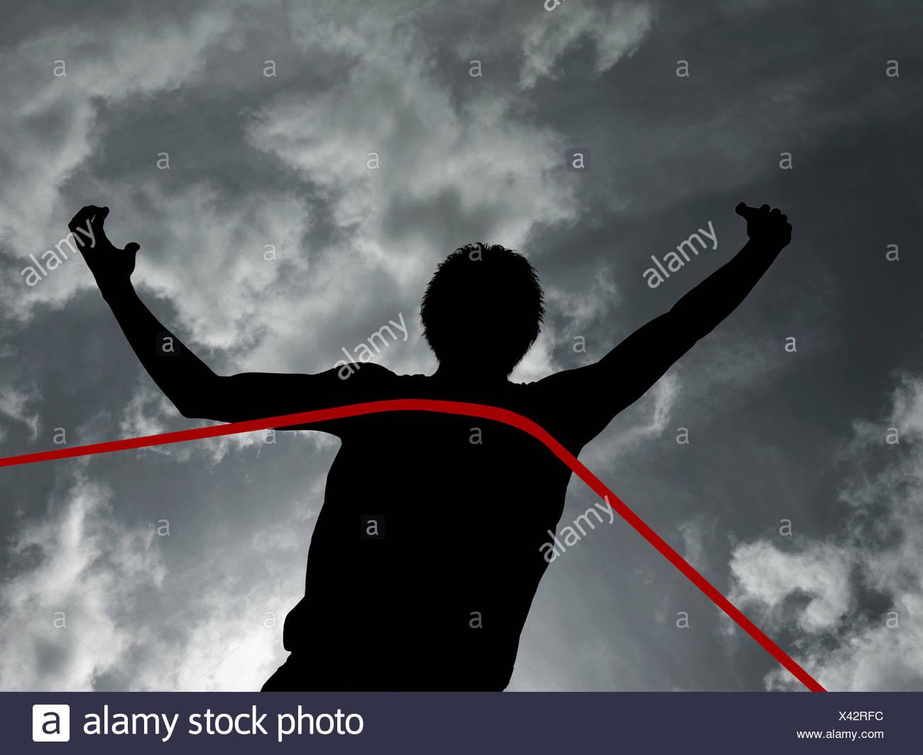 Silhouette di un atleta al traguardo Immagini Stock
