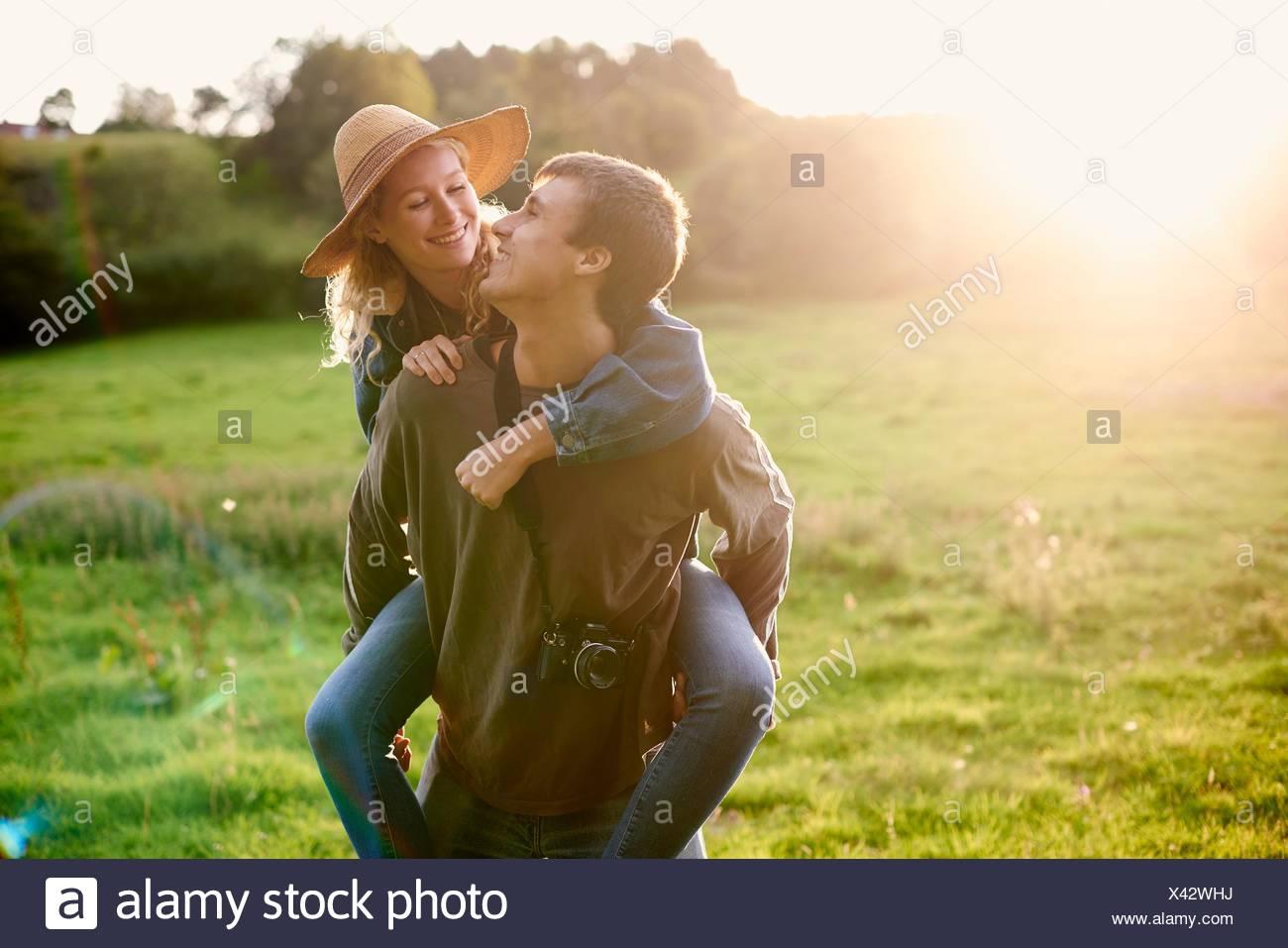 Giovane ragazza dando un piggyback in campo rurale Immagini Stock