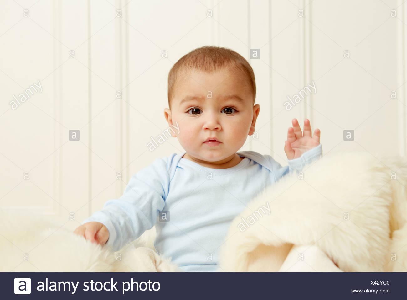 Baby sitter sul tappeto di pelle di pecora Immagini Stock