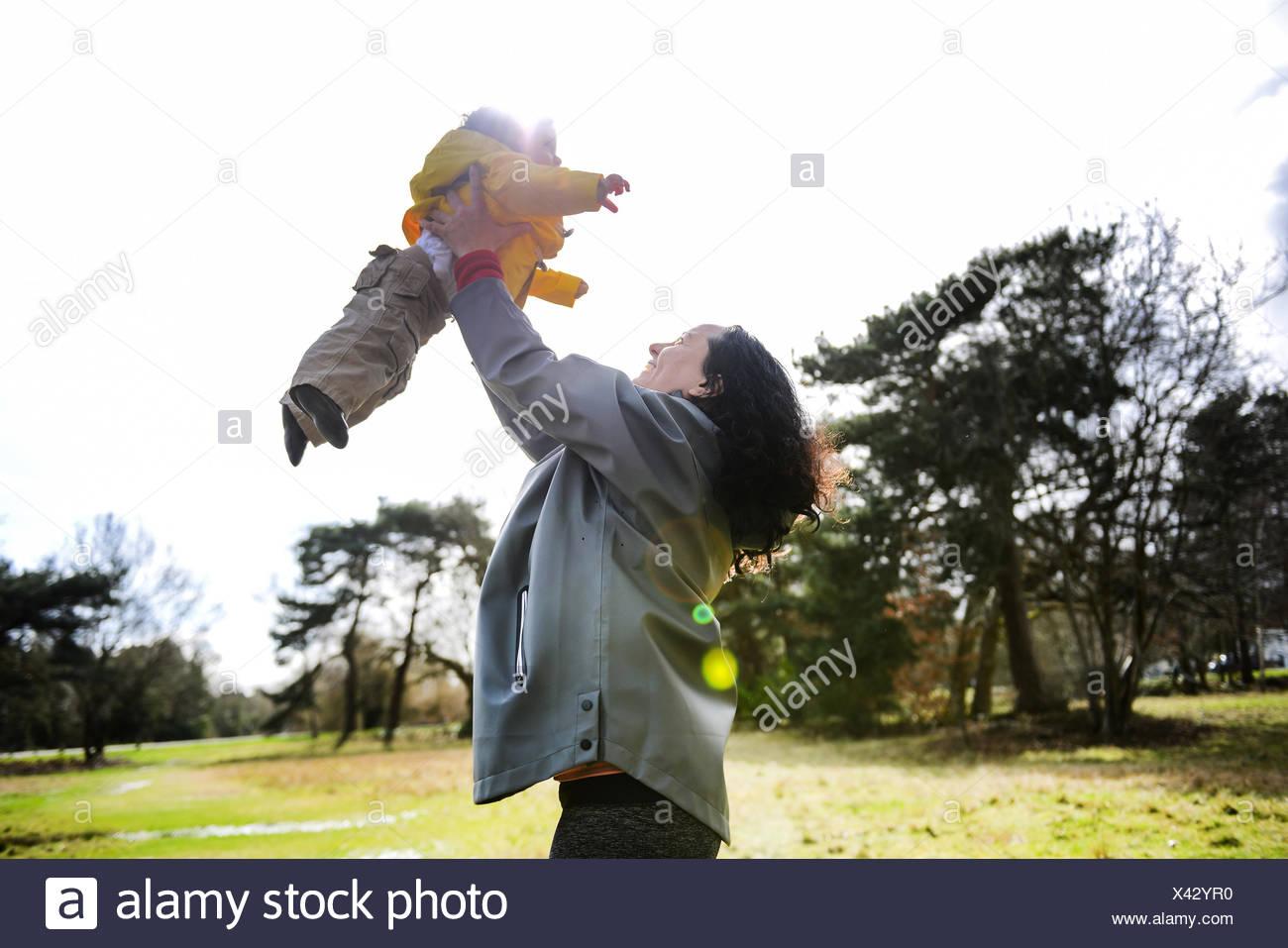 Donna matura tenendo premuto fino e giocare con il bambino figlio in posizione di parcheggio Immagini Stock