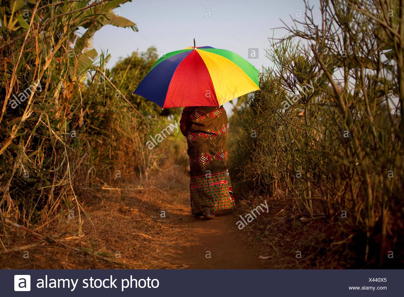 Vecchia donna in abito tradizionale camminando sul percorso con ombrello come protezione del sole , il Burundi, Karuzi, Buhiga Foto Stock