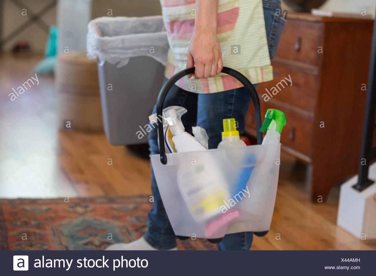 Giovane donna pulizia casalinga con verde di prodotti per la pulizia Immagini Stock