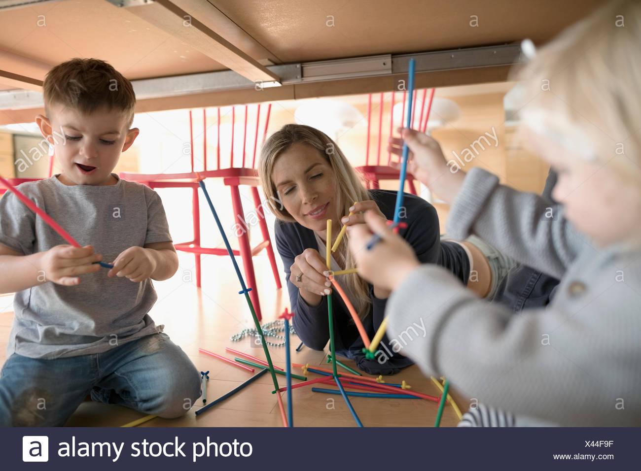 La madre e il bambino bambini che giocano con i bastoni del connettore sotto la tabella Immagini Stock