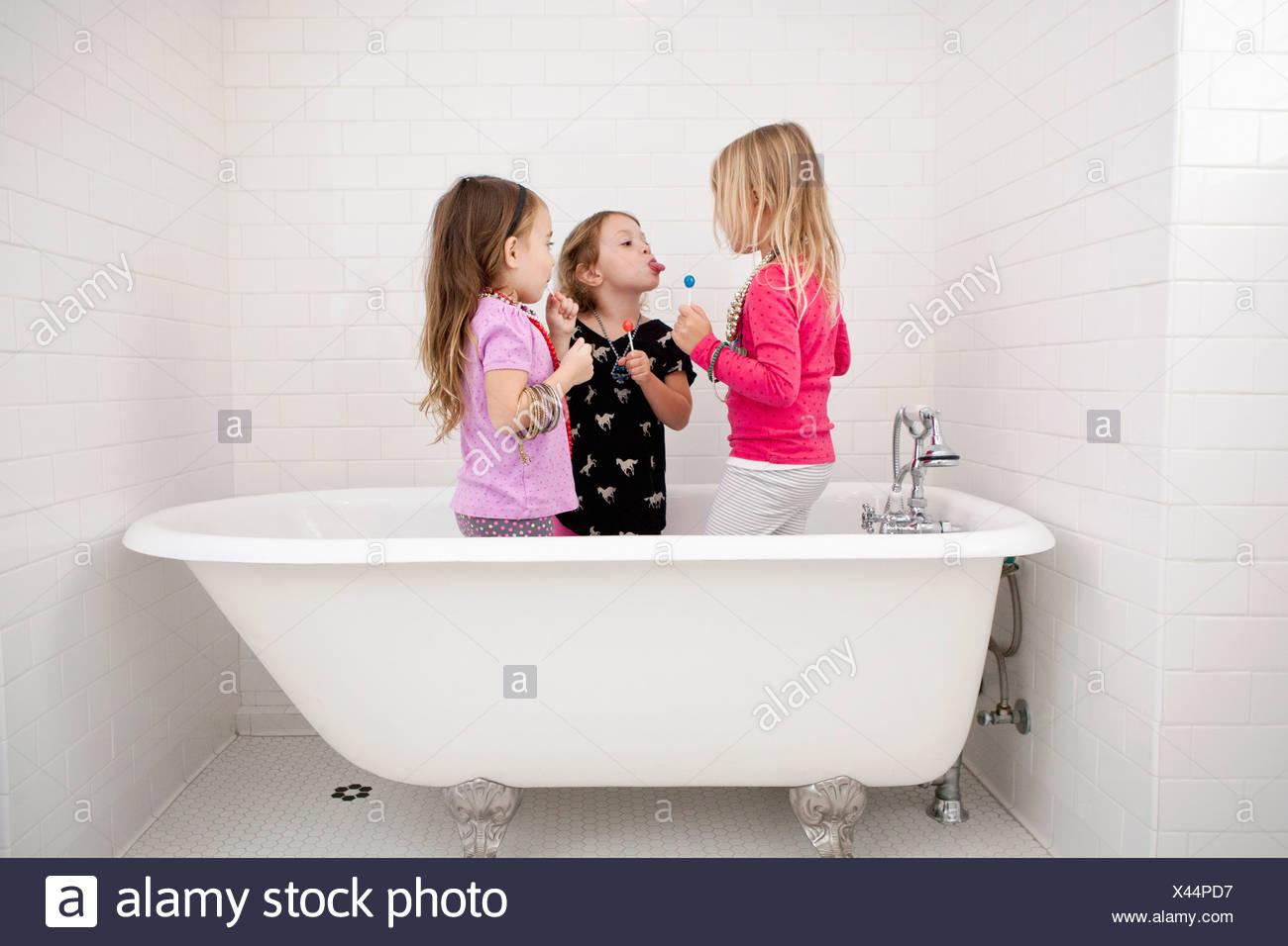 Tre giovani ragazze in piedi nella vasca da bagno con connettori lollipop Immagini Stock