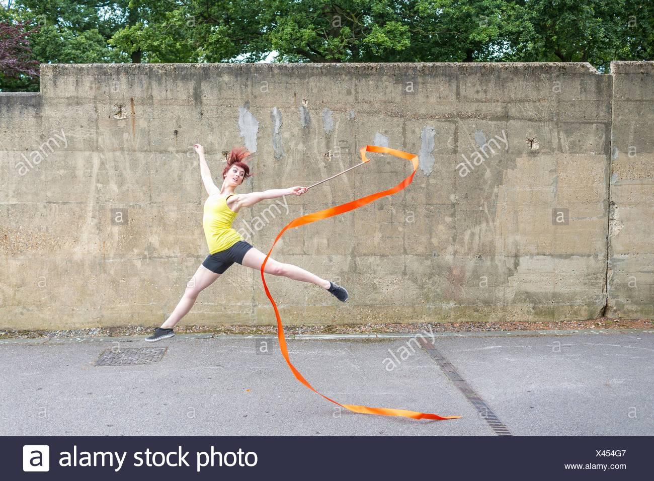 Giovane donna pratica di danza a nastro su corte Immagini Stock
