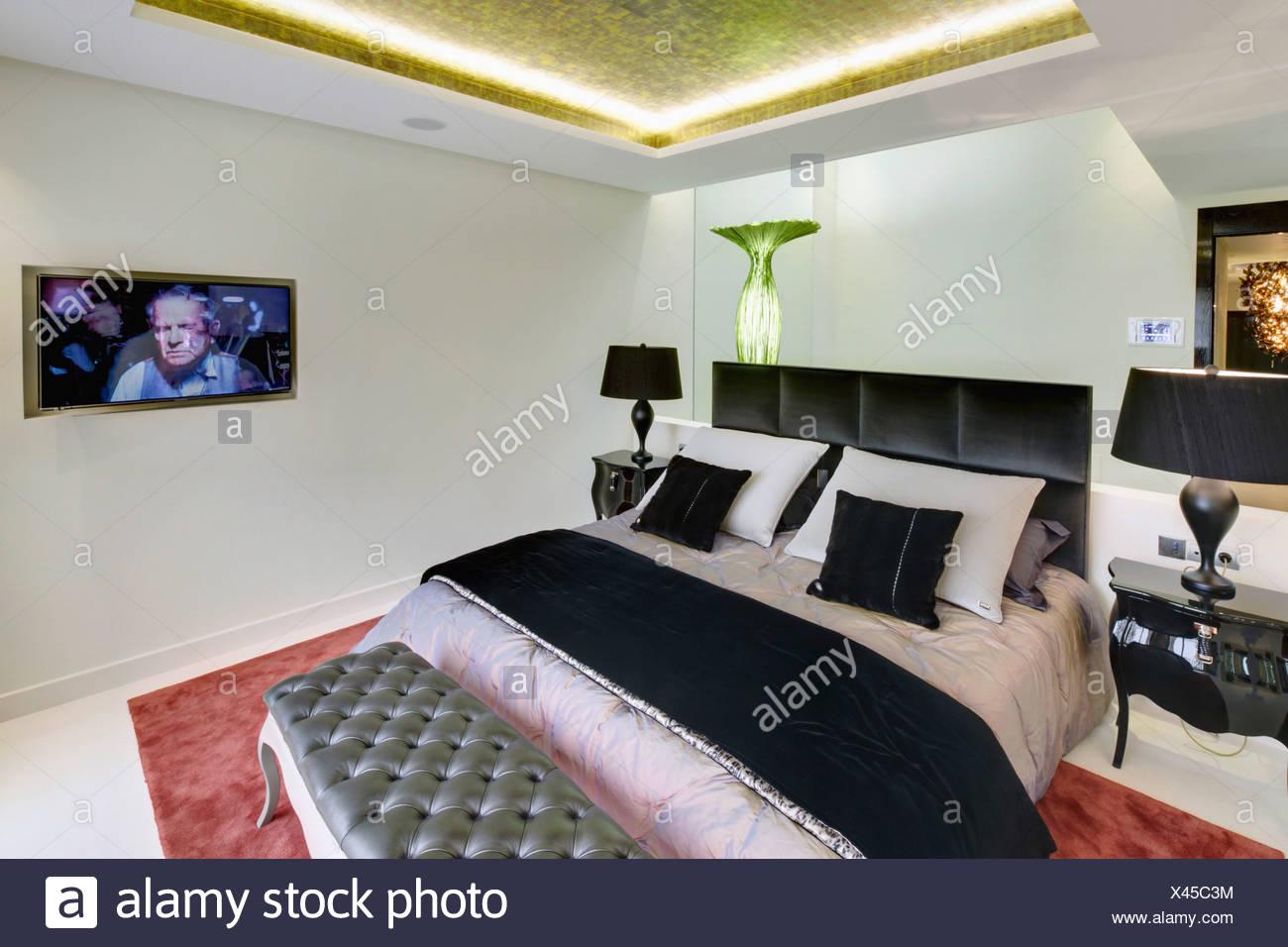 Nero piegato buttare sul letto con testiera in pelle nera in ...