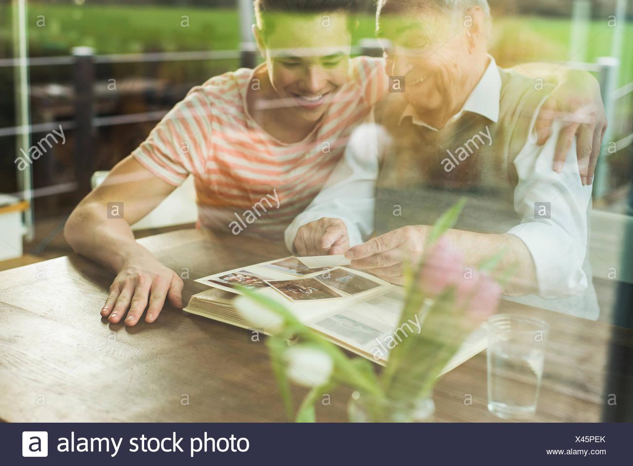 Nonno e nipote guardando vecchie fotografie insieme Immagini Stock