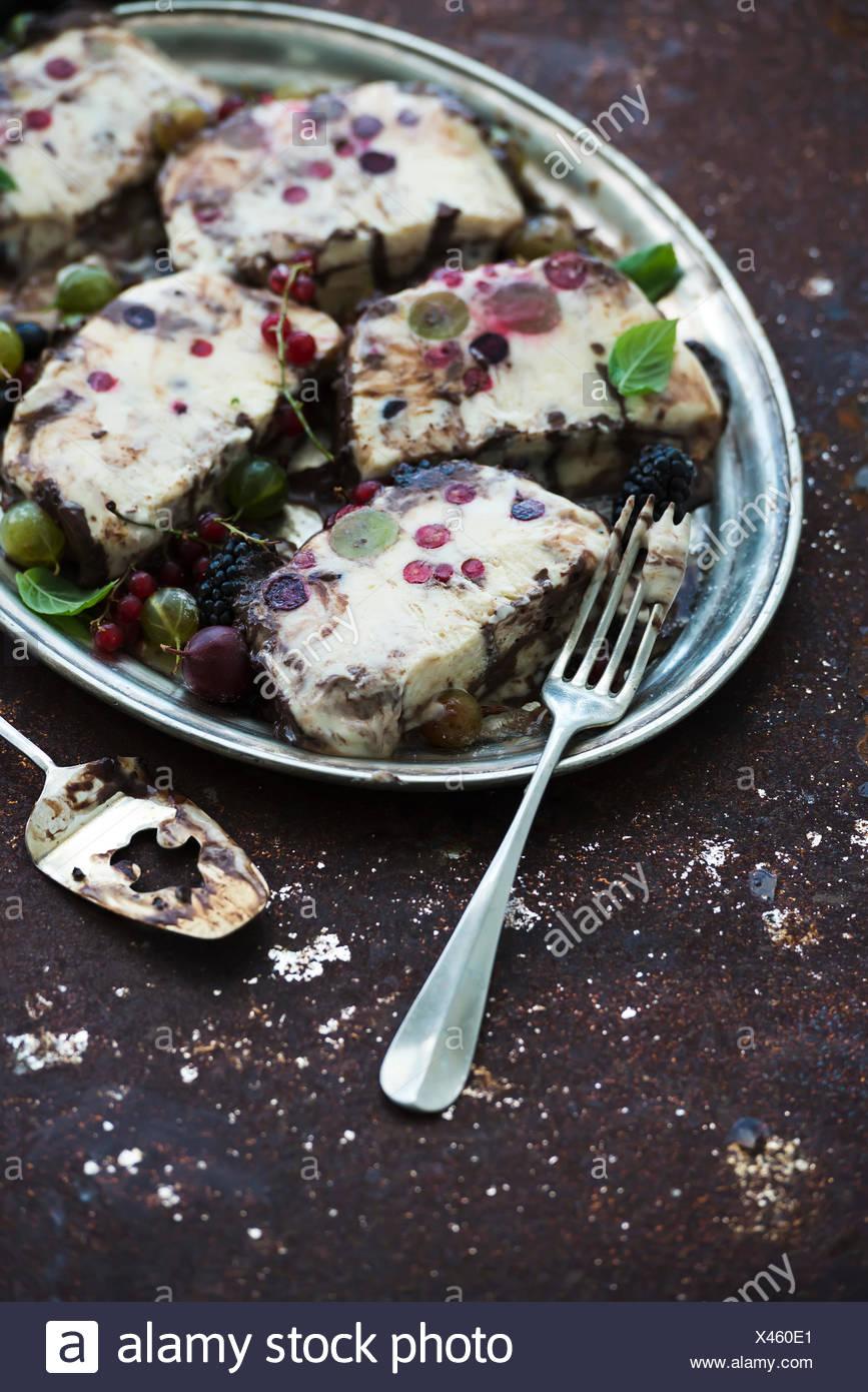 Semifreddi o formaggio italiano il gelato dessert con frutti di bosco giardino e menta su vintage vassoio d'argento su sfondo scuro, top vie Immagini Stock
