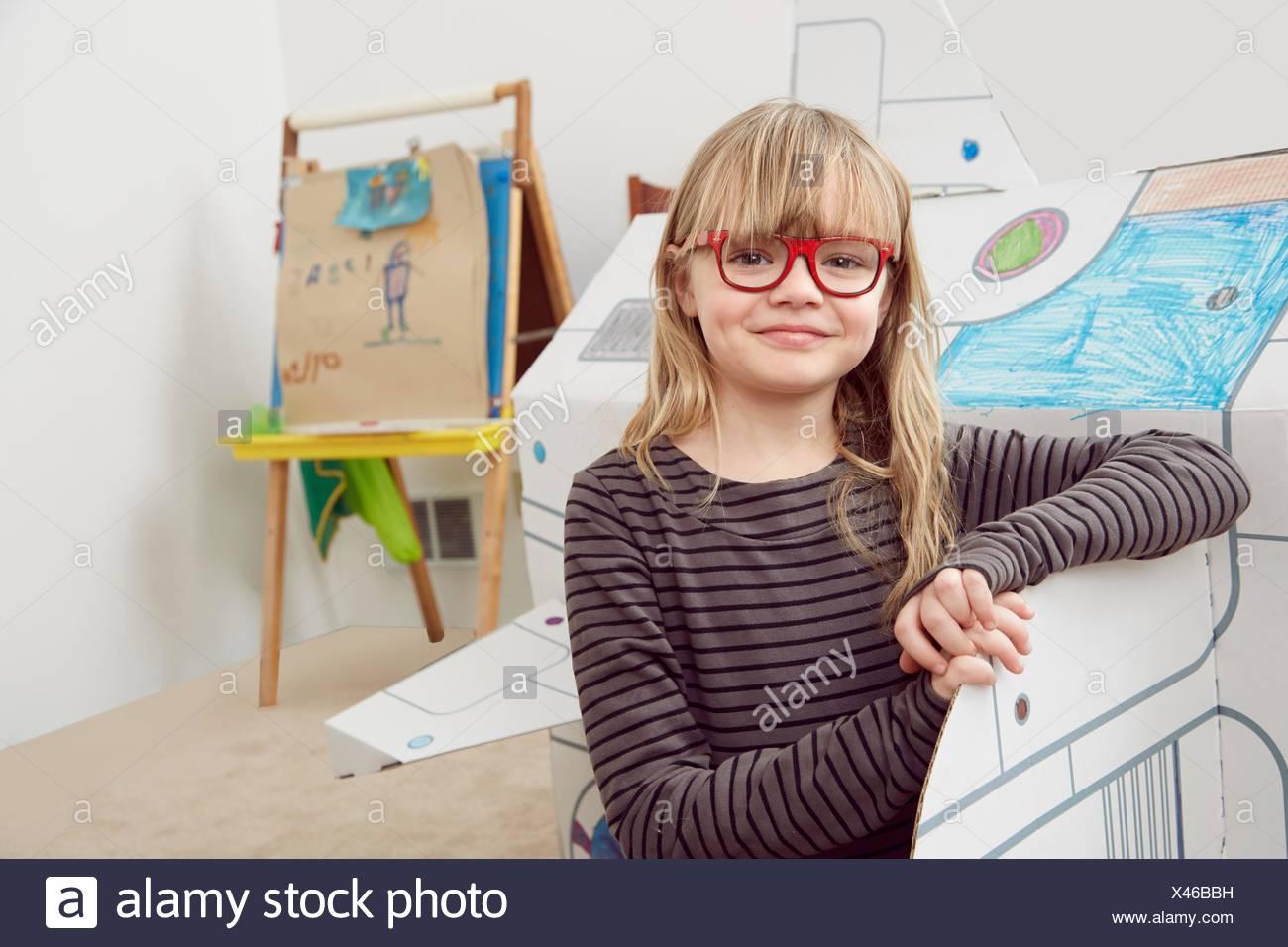 Ritratto di giovane ragazza in piedi accanto a astronave di cartone Immagini Stock