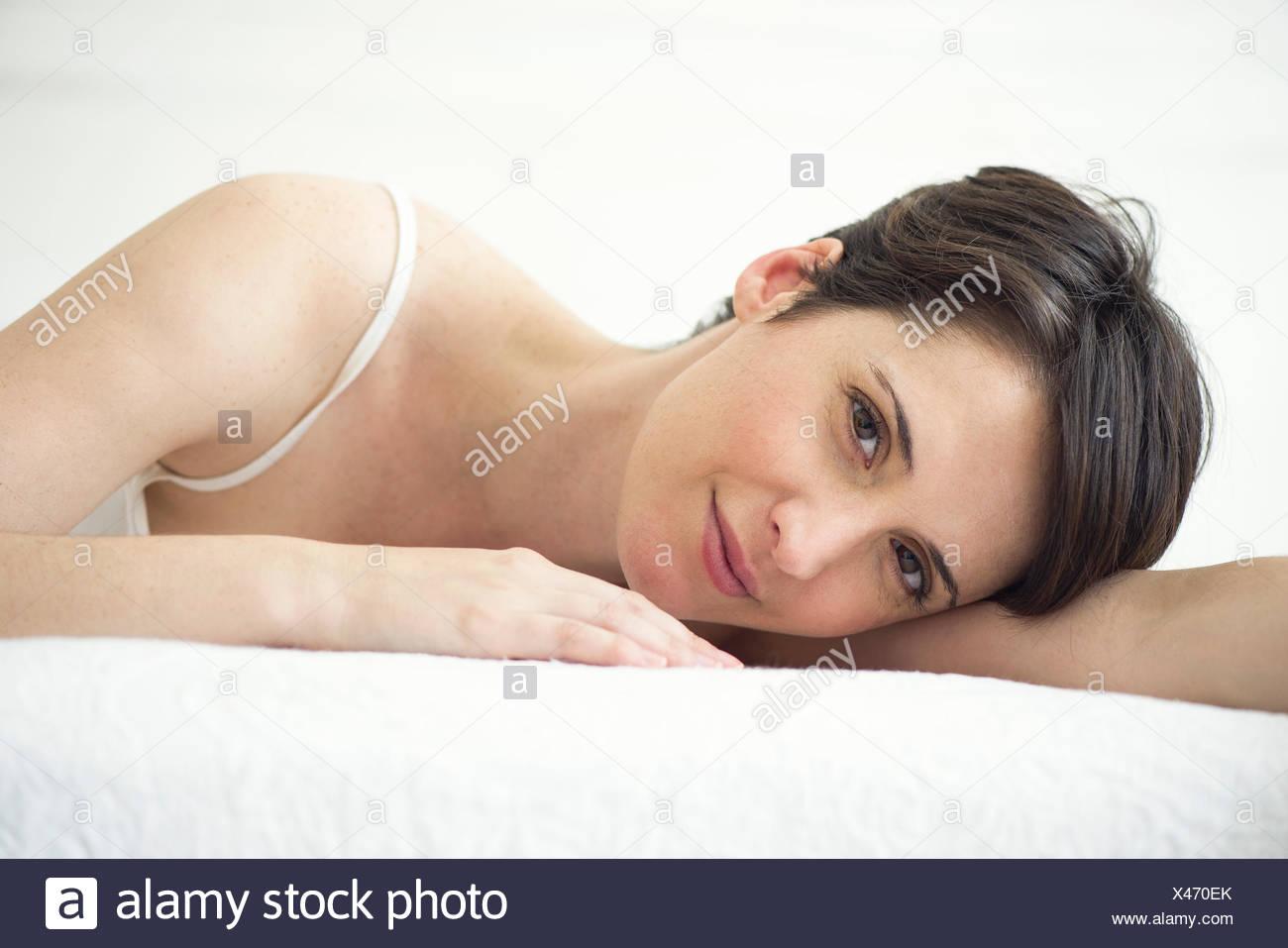 Donna in appoggio sul letto, ritratto Immagini Stock
