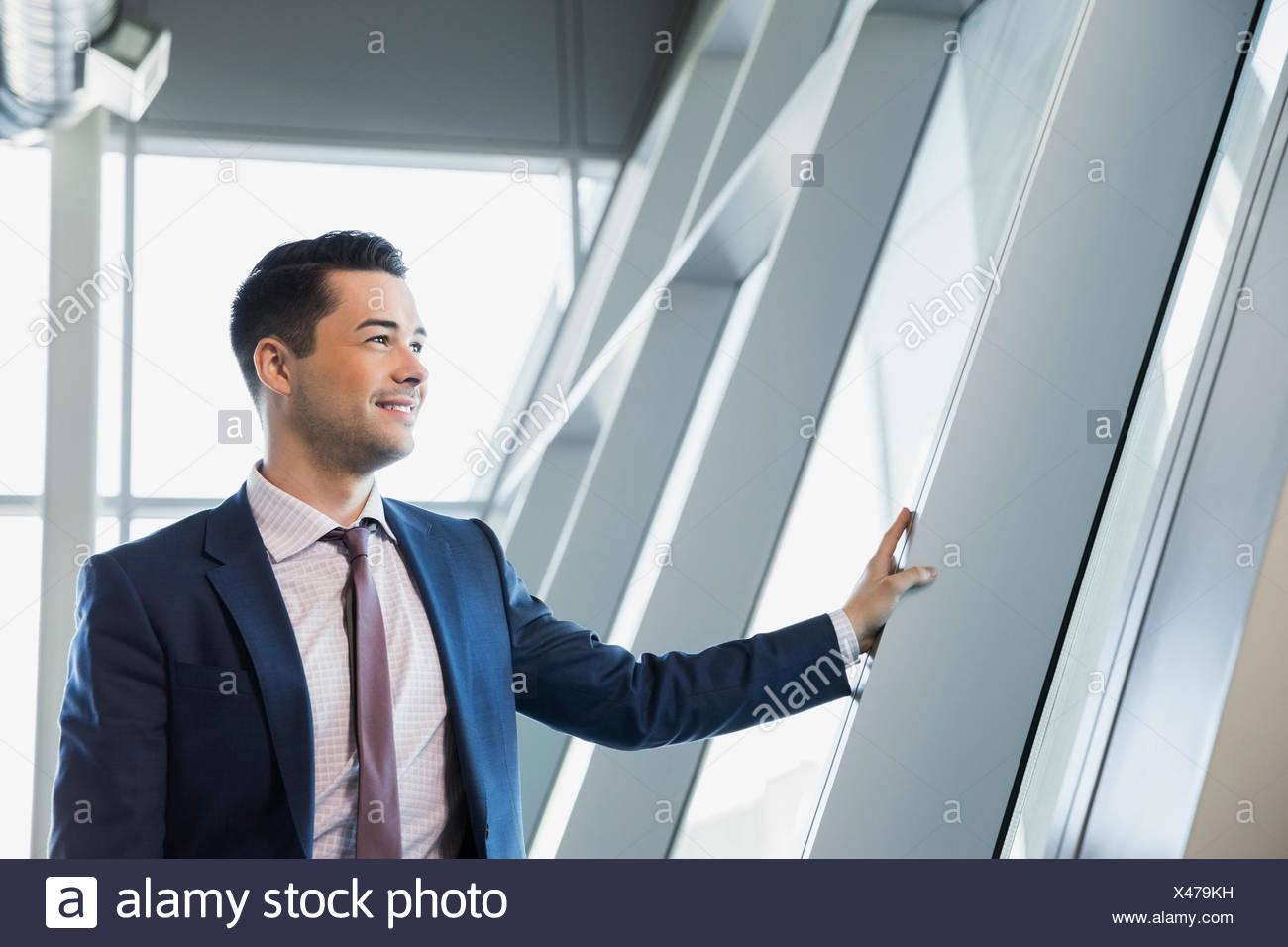 Imprenditore sorridente a guardare fuori dalla finestra Immagini Stock