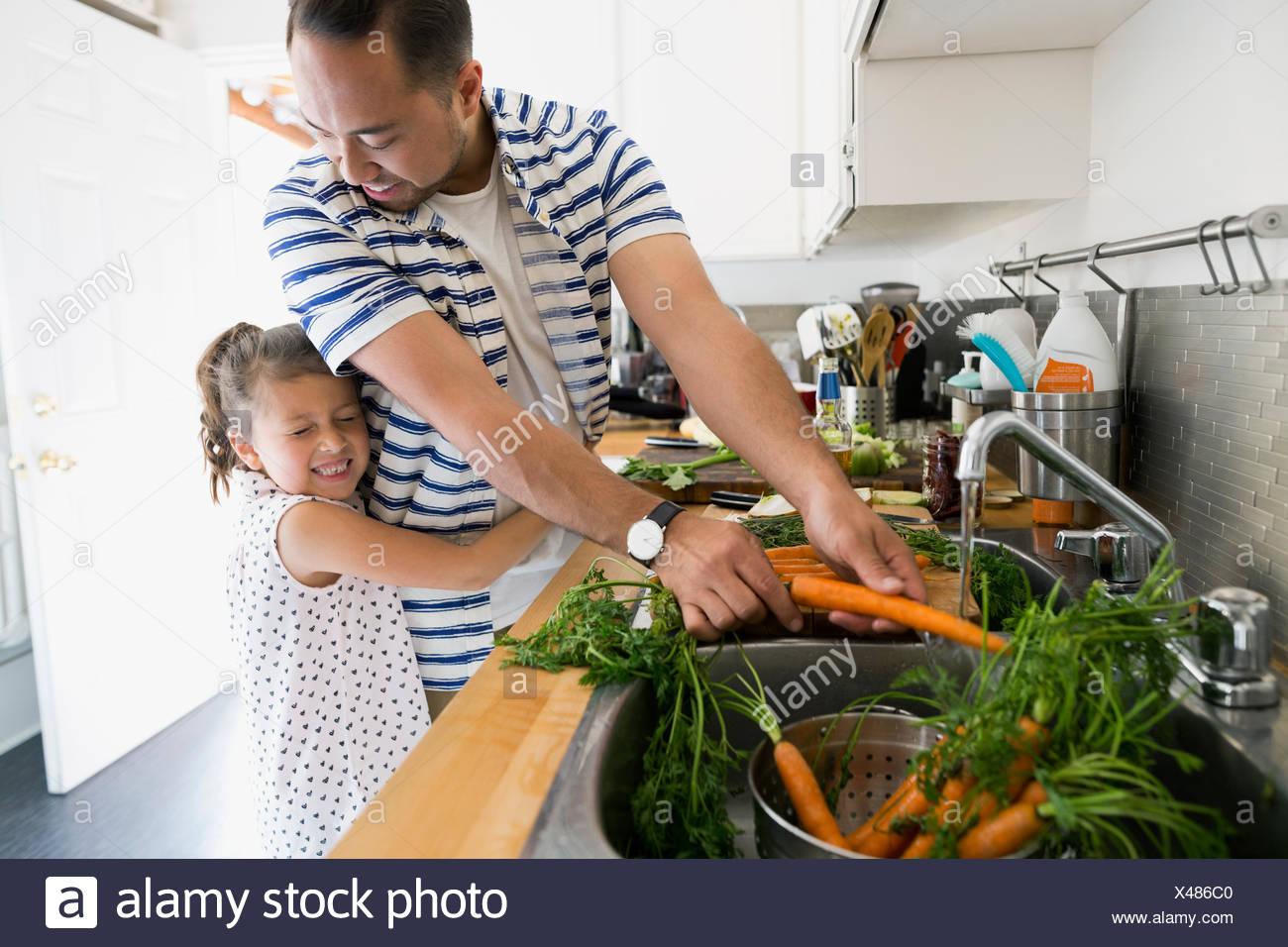Figlia di Padre abbracciando la cottura e il lavaggio di carote al lavello da cucina Immagini Stock