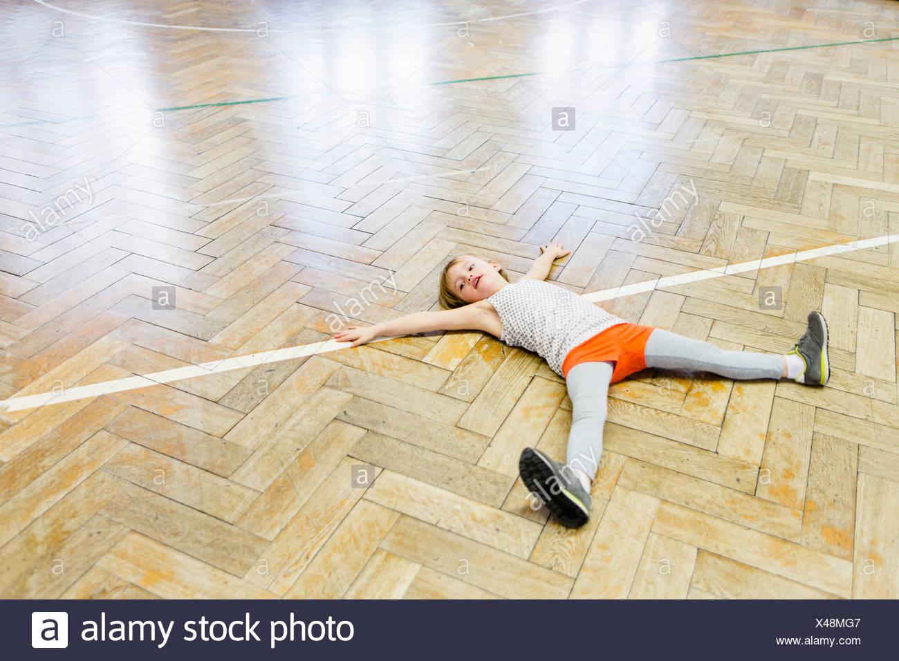Ragazza distesa sul pavimento in legno in school hall con braccia e gambe divaricate Immagini Stock