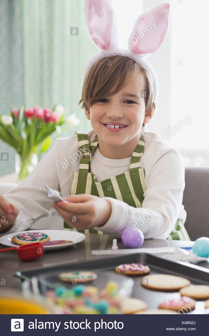 Ritratto di ragazzo indossa orecchie di coniglio decorazione di Pasqua i cookie Immagini Stock